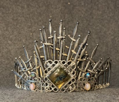 Silver tiara made from swords on a gray background