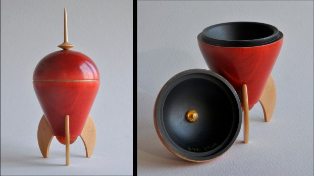 Spaceship-shaped maple wood box. Dyed red with gold ink accents and a black interior.