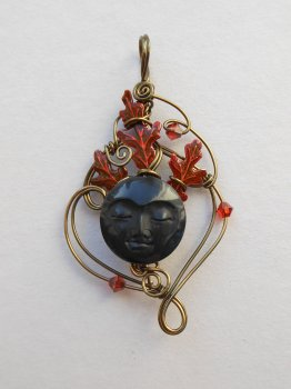 Antique brass wire pendant, red oak leaves behind a round black carved face